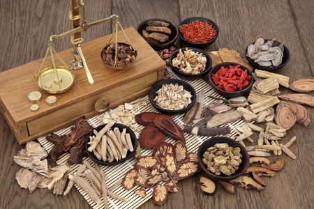 Photo pour Traditional chinese herb ingredients used in alternative herbal medicine with old brass scales over bamboo and oak background. - image libre de droit