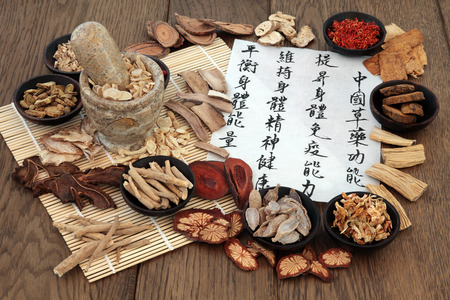 Photo pour Chinese herbal medicine with herb ingredients and calligraphy on rice paper. Translation reads as chinese herbal medicine as increasing the bodys ability to maintain body and spirit health and balance energy. - image libre de droit