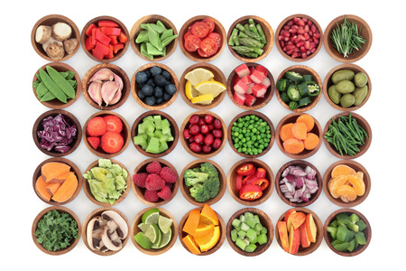 Photo pour Paleolithic super health food of fruit and vegetables in wooden bowls over white wood background. High in vitamins, antioxidants, minerals and anthocyanins. - image libre de droit