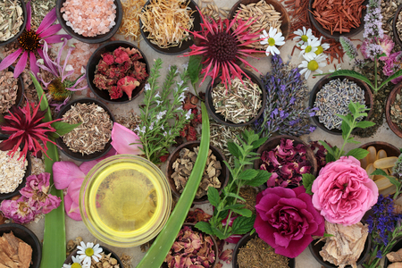 Natural herbal alternative medicine for skincare with fresh and dried herbs, flowers and almond oil on hemp paper background.