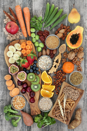 Foto de Health food concept for a high fiber diet with fruit, vegetables, cereals, nuts, seeds, whole wheat pasta, grains, legumes and spice. Foods high in omega 3, anthocyanins, antioxidants and vitamins on rustic background top view. - Imagen libre de derechos