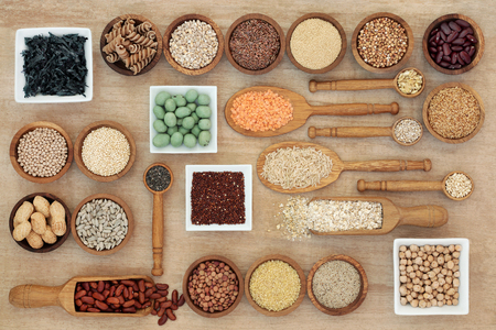 Foto de Dried macrobiotic diet health food concept with legumes, seaweed, grain, cereal, nuts, seeds and whole wheat pasta. High in smart carbohydrates, protein, antioxidants and fibre,  top view. - Imagen libre de derechos
