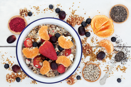 Healthy food for breakfast with granola, fresh fruit, nuts, pollen grain, yoghurt, acai berry powder and chia seed with foods high in omega 3, protein, antioxidants, anthocyanins, minerals and vitamins on  rustic white wood table background, top view.