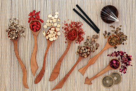 Foto de Chinese herbal medicine with herbs in wooden spoons, acupuncture needles and moxa sticks used in moxibustion therapy with feng shui coins on bamboo background. Top view. - Imagen libre de derechos