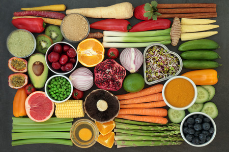 Foto de Health food for clean eating concept with fresh fruit, vegetables, dairy, supplement powders, herbs and spices.  High in antioxidants, anthocyanins, vitamins and dietary fibre. Flat lay. - Imagen libre de derechos