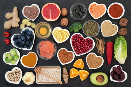 Photo for Super food to slow the ageing process concept including fish, fruit, vegetables, herbs, spices, supplement powders honey & dairy on slate. High in antioxidants, anthocyanins, dietary fibre & vitamins. - Royalty Free Image