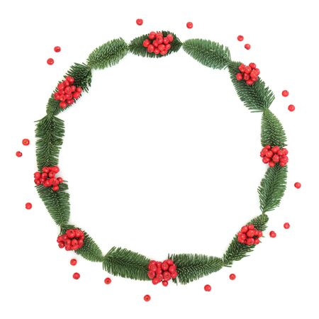 Photo for Winter and Christmas holly berry and spruce fir wreath with loose berries on white background with copy space. Traditional symbol for the festive season. - Royalty Free Image
