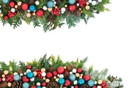 Photo pour Festive Christmas background border with red, blue and silver ball bauble decorations and winter flora with pine cones on white with copy space.  - image libre de droit