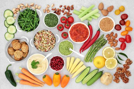 Foto de Health food for a vegan diet with falafel meatball substitute, fruit, vegetables, seeds, nuts & dips. High in vitamins, minerals, antioxidants, anthocyanins, protein, fibre, omega 3 & smart carbs. Flat lay. - Imagen libre de derechos