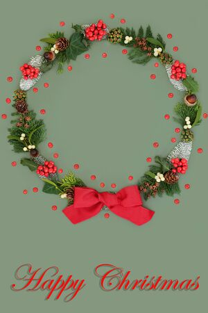 Photo for Happy Christmas wreath with a variety of flora and fauna and loose holly berries with red bow on green background and title. - Royalty Free Image