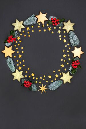 Photo for Christmas wreath abstract decoration with gold stars and baubles, holly and winter flora on dark grey background with copy space. Decorative symbol for the festive season. - Royalty Free Image