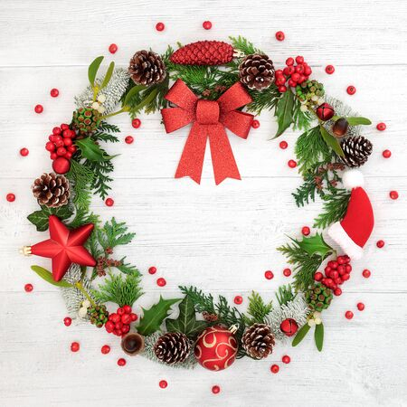 Photo for Christmas wreath with red bow, bauble decorations, winter flora and loose holly berries on rustic wood background. - Royalty Free Image