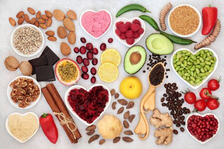 Photo for Healthy heart food for vitality with fruit, vegetables, nuts, dips, spice & herbs, high in fibre, antioxidants, vitamins, omega 3 & protein. Support for the cardiovascular system with low GI. Flat lay - Royalty Free Image