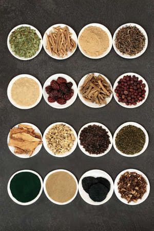 Photo pour Herbs for energy, vitality & fitness used in natural alternative & chinese herbal medicine. In white porcelain bowls on grunge background. - image libre de droit