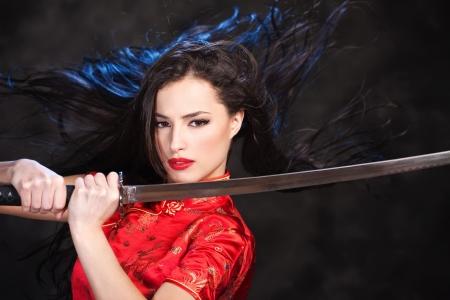 Pretty kimono woman in action with katana/sword