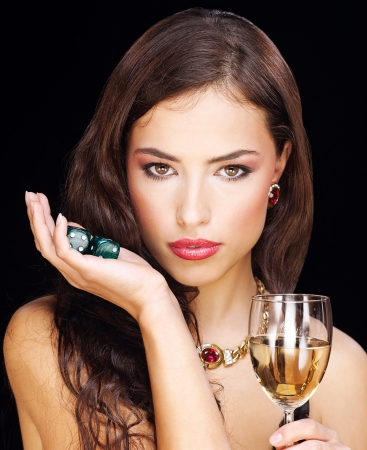 pretty young woman holding gamble dices and wine on black background