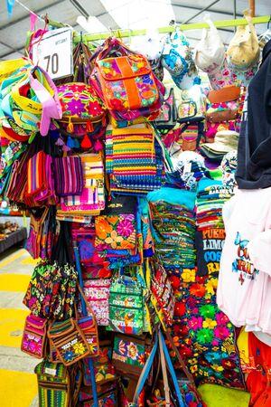 Photo pour Puerto Limon, Costa Rica - December 8, 2019: Ethnic souvenirs, baseball caps, bags with various pattern hanging in street market - image libre de droit