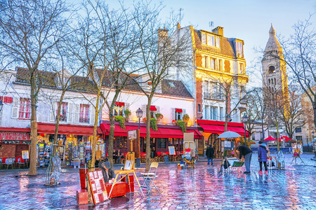 Foto de Place du Tertre in Montmartre in Paris. In area lot of souvenirs and handicrafts. In small houses are located cafes, restaurants and art galleries. - Imagen libre de derechos