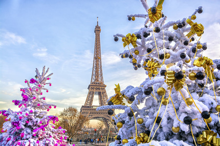 Foto de Eiffel Tower is the main attraction of Paris on the background of decorated Christmas trees in December. Travel Greeting Card with Christmas in Paris, France - Imagen libre de derechos