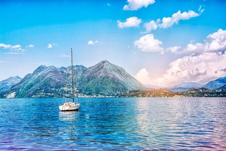 Photo pour Beautiful landscape of the Alpine mountains on the Lago Maggiore lake against the background of a cloudy blue sky, ItalyBeautiful landscape of the Alpine mountains on the Lago Maggiore lake against the background of a cloudy blue sky, Italy - image libre de droit