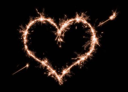 Photo pour Sparklers heart on a black background. - image libre de droit