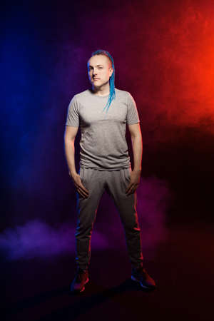 Photo for A man with a braided mohawk haircut calmly posing holding hands in pockets of sweatpants against a background of smoke. - Royalty Free Image