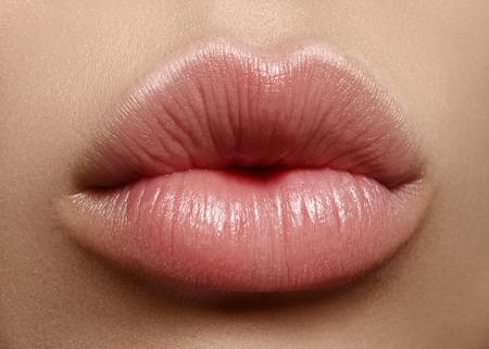 Close-up perfect natural lip makeup beautiful female mouth. Plump sexy full lips. Macro photo face detail. Perfect clean skin, fresh lip make-up. Beautiful spa tender lips