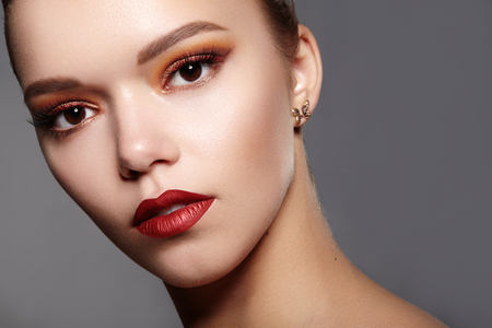 Photo pour Beautiful Woman with Professional Makeup. Party Gold Eye Make-up, Perfect Eyebrows, Shine Skin. Bright Fashion Look with Red Lips - image libre de droit