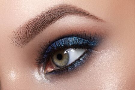 Photo pour Closeup Macro of Woman Face with Blue Eyes Make-up. Fashion Celebrate Makeup, Glowy Clean Skin, perfect Shapes of Brows. Shiny Simmer and Rouge - image libre de droit