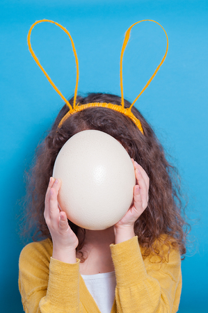 Photo for Cheerful little child girl with bunny ears with ostrich egg on a colored background. Happy Easter - Royalty Free Image