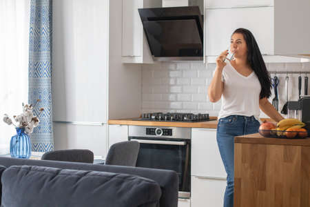 Photo pour A young brunette woman in jeans and a white T-shirt drinks water in the kitchen. - image libre de droit