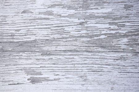 Photo pour A wooden surface with cracks and peeling white paint. Texture. Background. Close-up. Selective focus. Copy space. - image libre de droit