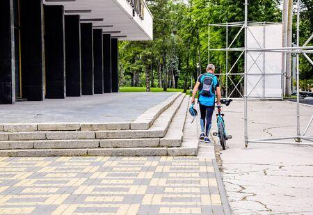 Photo pour An amateur cyclist rides bicycle and goes to city park. Special sports uniform with safety helmet. Warm summer day. Healthy lifestyle concept. Selective focus. Copy space. - image libre de droit
