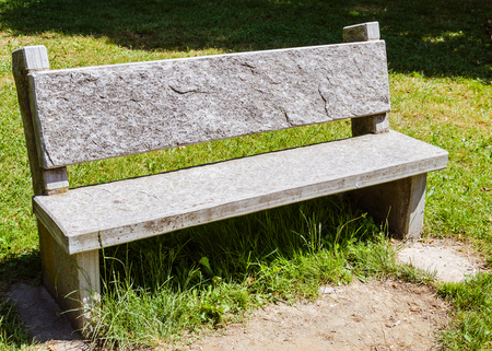 view of a stone beanch on a public park