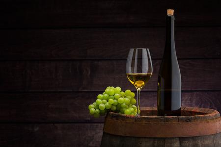 Foto de white wine bottle and wine glass on wodden barrel - Imagen libre de derechos