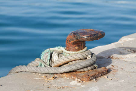Photo for Iron pole for mooring of ships at pier, old rusty iron bollard on a pier on the coast of Andalucia, Spain. Landscape with sea wharf. - Royalty Free Image