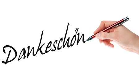 Hand with pen writing the german word thank you
