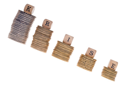 Stack of coins and wood dice with the german word crisis