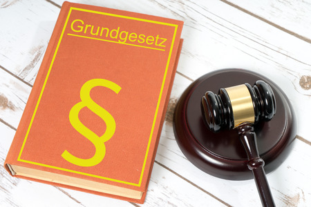 Statute book with the German words fundamental law and Judges gavel