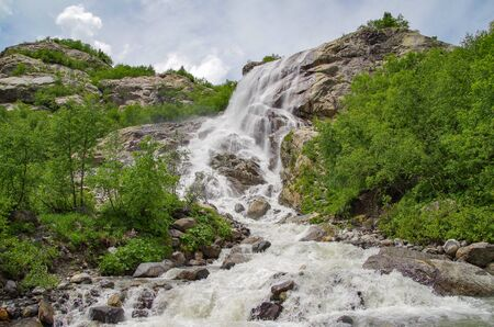 Dombay. Alibek Fall. Waterfall formed by falling of river from Alibek Glacier. Stones from which water falls - roches moutonnees. Russia, North Caucasus, Karachay-Cherkessia, Teberda Nature Reserve