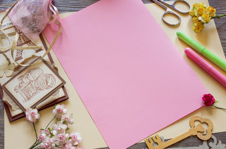 Top view of  paper roses and a pink sheet of paper. Making handmade cards