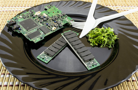 Consumer electronics concept for the appetite of buyers in electronic industry, with printed circuit board and microchips on a plate served with chopped parsley