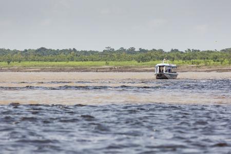 MANAUS, BRAZIL, OCTOBER 17: Typical wooden white Amazon boat sailing on Rio Negro near Manaus, Amazonas State. Brazil 2013