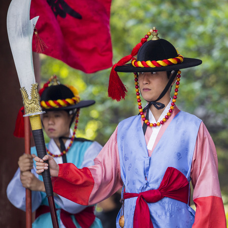 SEOUL, SOUTH KOREA - OCTOBER 20, 2016: Palace guards in traditional costumes solemnly guard the imposing main gate of Deoksugung Palace in downtown Seoul, South Korea.