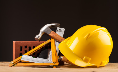 yellow helmet brick and builder tools on wooden table