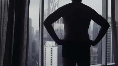 Foto de Fat man stay against window and look to urban city view from high floor. - Imagen libre de derechos