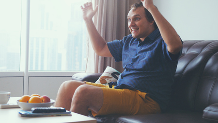 Photo pour Handsome exited man watching a football match in his living room by the window - image libre de droit