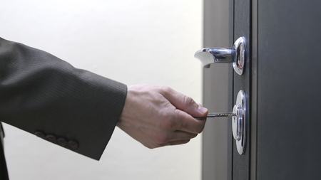 Photo for Close up of a man hand unlocks a houses door with key - Royalty Free Image