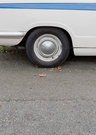 Close-up of wheel tyres of white vintage car with pale blue stripe.