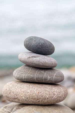 Photo pour Pyramid of sea stones on the seashore at the pebble beach. Concept of harmony and balance. - image libre de droit